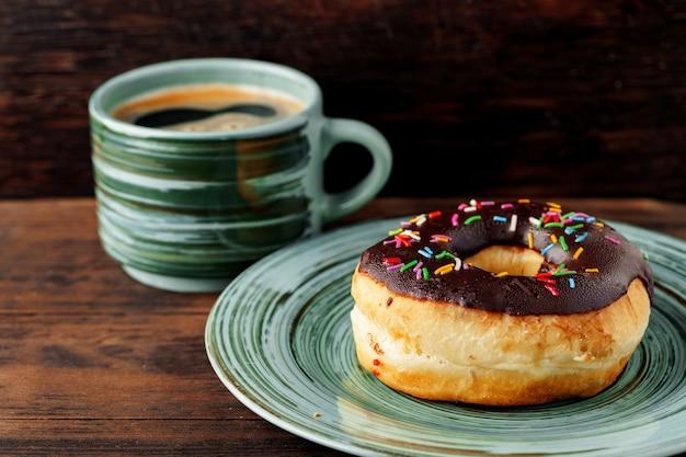 一杯のコーヒーと緑のプレート上の艶をかけられたドーナツのクローズアップ