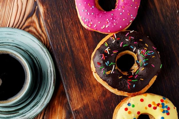一杯のコーヒーと緑のプレート上の艶をかけられたドーナツ
