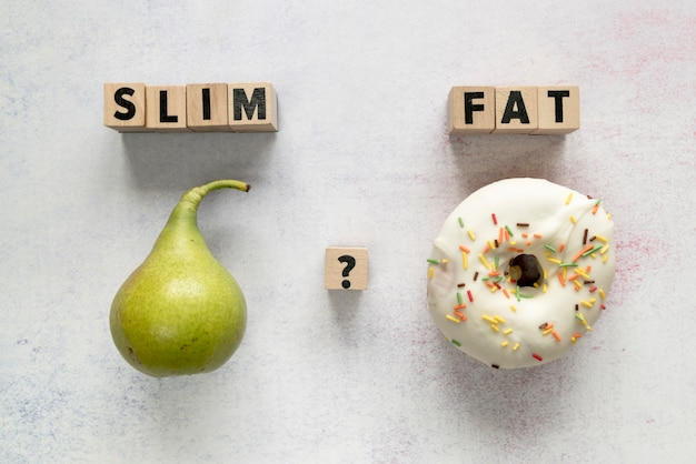 Glazed donut; pear and slim; fat text with question mark on wooden block over concrete surface