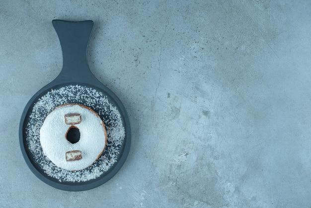 Глазированный пончик в сервировочном противне на мраморе.
