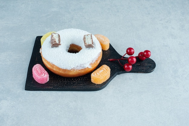 Glazed donut and sugary marmelades on a board on marble.