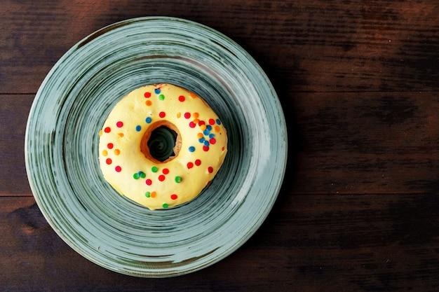プレートに振りかける艶をかけられたドーナツは上面図をクローズアップ