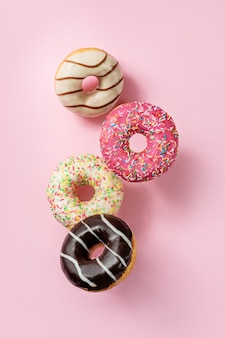 Глазированные пончики, парящие на розовом фоне.