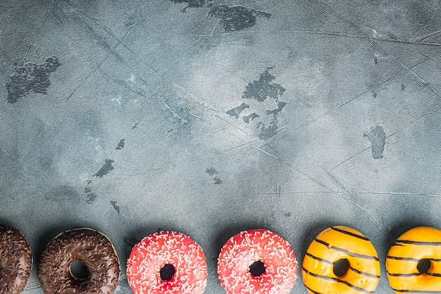 艶をかけられたドーナツセット、灰色のテーブル、コピースペース付きの上面図フラットレイ
