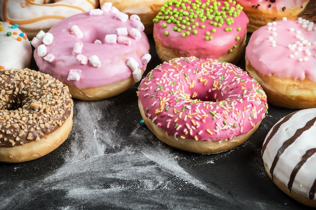 Glazed donuts with different fillings on a black