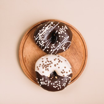 Glazed donuts on wooden board on table