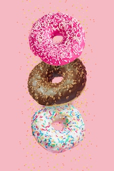 Glazed doughnuts in motion falling on pink with colorful sprinkles