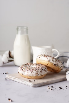 Glazed doughnuts with sprinkles and milk bottle