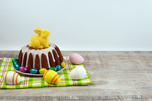 Glazed easter cake decorated with eggs and yellow bunny