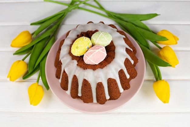 Глазированный пасхальный кулич, украшенный конфетами из яиц и желтыми тюльпанами