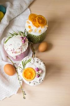 木製のテーブルにオレンジと卵で飾られた艶をかけられたイースターケーキハッピーイースターホリデー