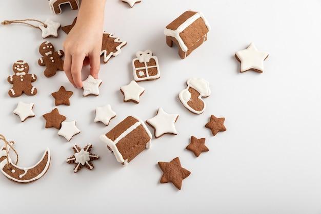 白いテーブルと子供の手に艶をかけられたジンジャーブレッドクッキー。クリスマスの準備。上面図。
