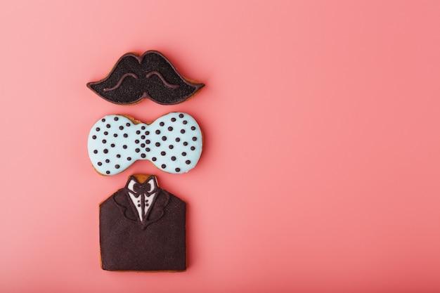 口ひげ、蝶、タキシードの形をした艶をかけられたジンジャーブレッドは、男性のセットを主演します。手作りのクッキー。
