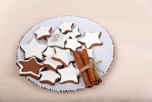 釉薬をかけたジンジャーブレッドの星とシナモンスティックを皿に。クリスマスのクッキー。