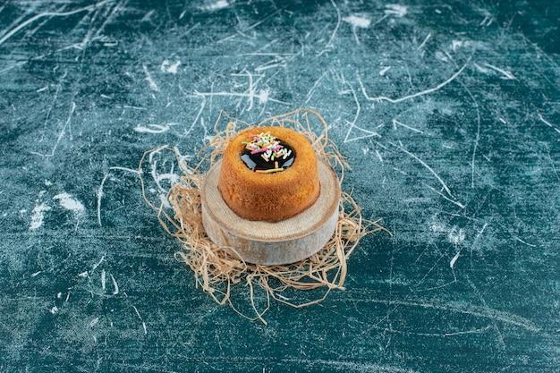 青の背景に、ボード上の艶をかけられたミニケーキ。高品質の写真