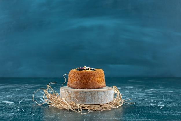 青いテーブルの上に、ボード上の艶をかけられたミニケーキ。