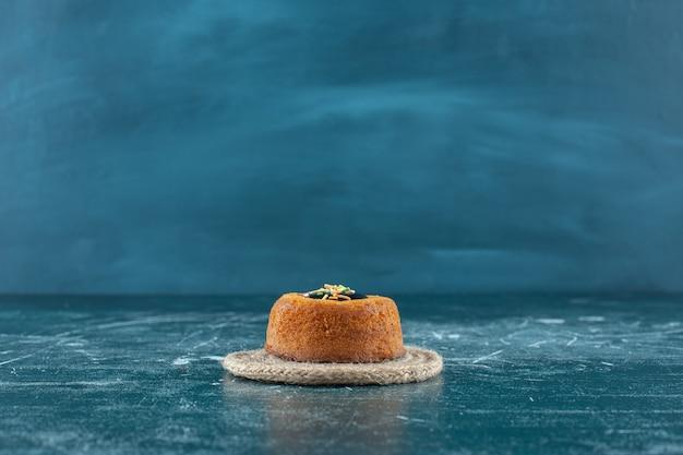 青い背景に、トリベットの艶をかけられたミニケーキ。高品質の写真