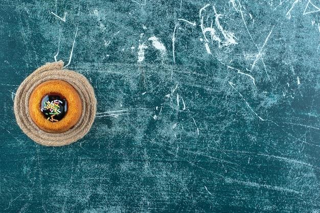 青いテーブルの上に、トリベットの上に艶をかけられたミニケーキ。