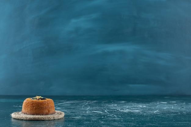 Mini cake glassata su sottopentola, sulla superficie blu
