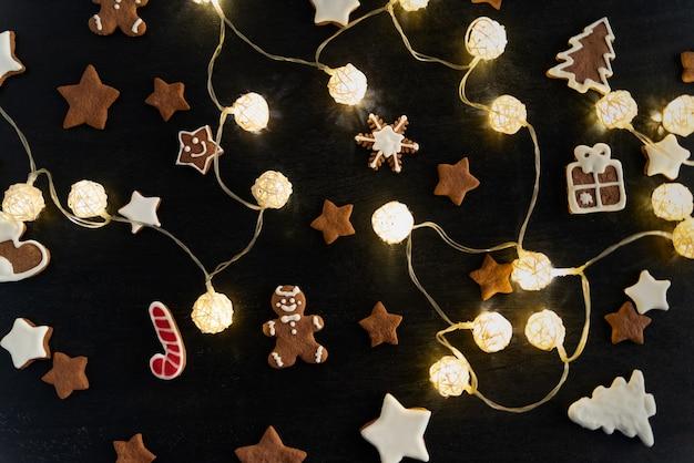 艶をかけられた塗られたクッキー:星、ジンジャーブレッドマン、雪片、モミの木と輝くクリスマスの花輪。