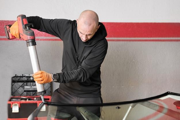 차고의 앞 유리에 고무 씰링을 적용하는 glazier를 닫습니다. 고품질 사진
