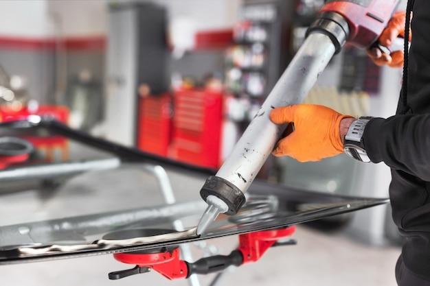 ガレージのフロントガラスにゴム製のシーリングを適用しているガラス工、クローズアップ。