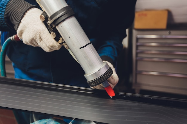 Стекольщик, применяя резиновое уплотнение к лобовому стеклу в гараже