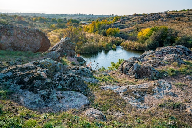 A gleaming beautiful little river among large white stones and green vegetation on the hills in ukraine