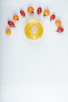 Gleaming red and yellow tomatoes on white background with bottle of oil. high quality photo