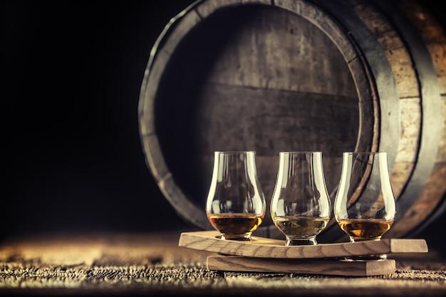 Чашки для дегустации виски glencairn на деревянной подаче, с бочкой для виски на темном фоне.