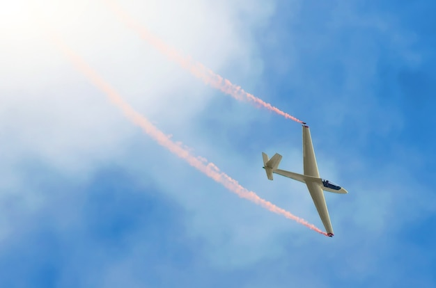 Glider airplane flying high in the sky with a trace of red smoke.