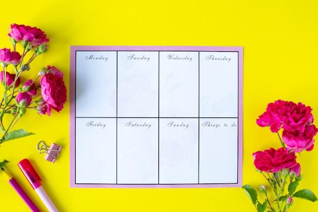 Планер с примечаниями и списком дел на желтом фоне с розовыми канцелярскими товарами и цветами. бизнес-концепция вид сверху