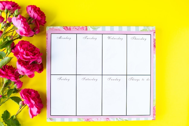 Glider with notes and to-do list on a yellow background with pink stationery and flowers. business concept. top view
