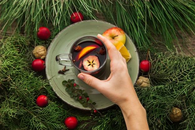 전나무 가지와 함께 휴가를 위한 집에서 만든 뜨거운 알코올 음료 컵에 반짝임