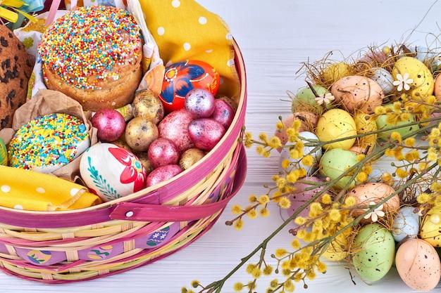 반짝이는 계란과 부활절 케이크 바구니. 흰색 바탕에 버드 나무와 달걀 화 환입니다.