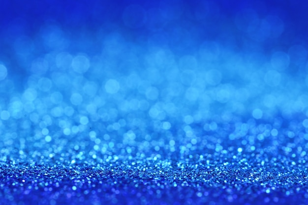 Glitter blue background with light blue shining bokeh.