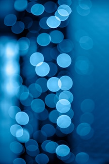 Glitter bokeh of night lights of classic blue garlands of 2020. vertical background for creativity and design.