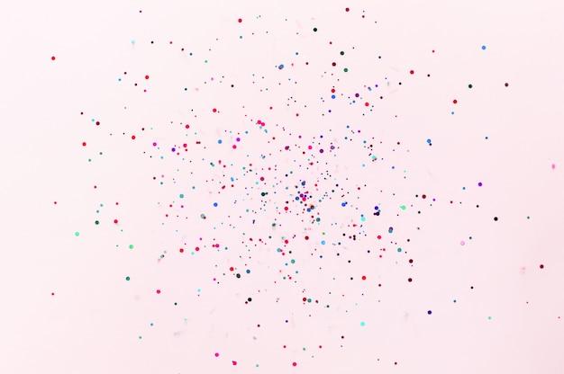 Блеск летающих блесток на розовом фоне пастельных модных.