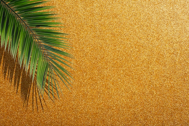 Glitter gold background. golden festive bright glamorous background with tropical palm leaves and shiny sparkles. high quality photo