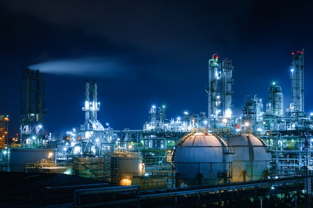 Glitter lighting of petrochemical industrial plant at night with gas storage sphere tanks and smoke stack