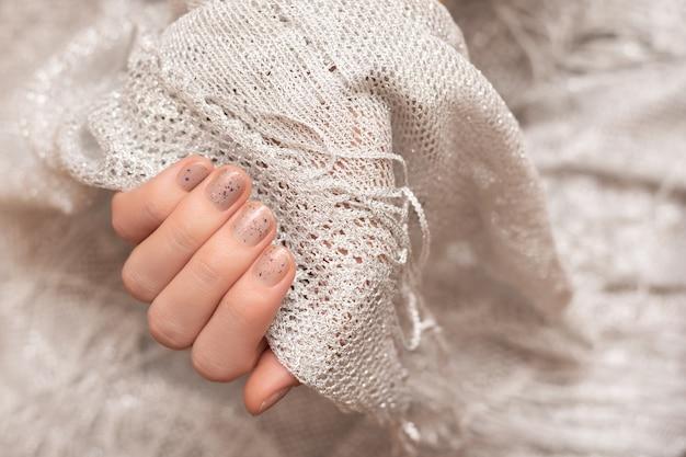 반짝이는 네일 디자인. 회색 매니큐어와 여성 손입니다.