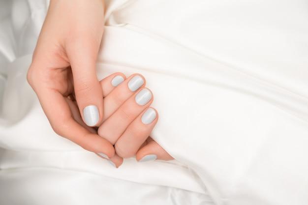 Блеск дизайна ногтей. женские руки с серым маникюром.