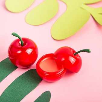 Glitter rumble in a cherry-shaped jar on a bright pink background among paper tropical leaves