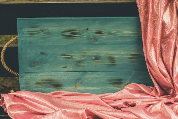キラキラスパンコールピンク。ピンクのキラキラ生地とウッドグリーンの背景