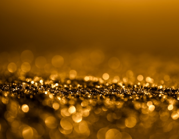 Glitter sparkle vintage lights background. dark gold and black. defocused .