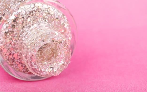 Glitter transparent nail polish on a pink background close up.