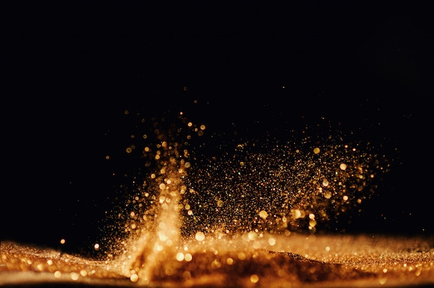 Glitter vintage lights background. gold and black. de focused