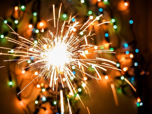 カラフルな背景のボケ味に輝く燃える線香花火。