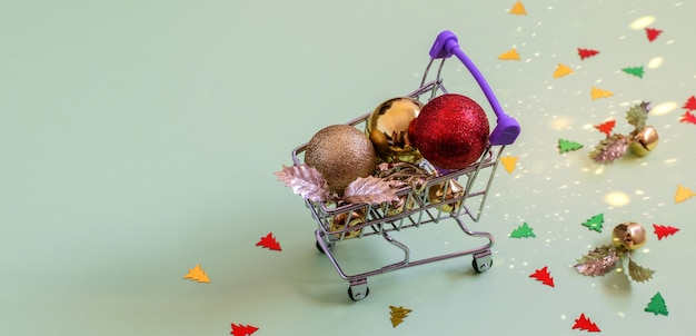きらびやかなクリスマスのおもちゃ。ミニショッピングカートの金色と赤のボール、つまらないもの、紙吹雪。