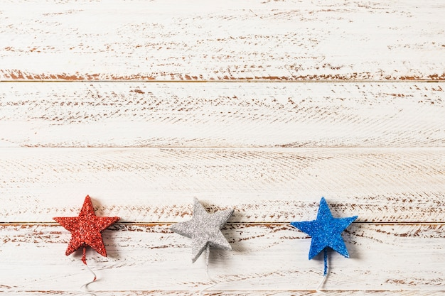 Glittering silver; red and blue stars on white wooden textured background